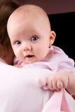 Bebé curioso en hombro de los padres Imagen de archivo