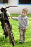Bebé curioso que camina alrededor de la bici vieja Imagenes de archivo