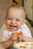 Bebé curioso que come un albaricoque Fotografía de archivo