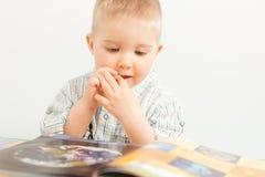 bebé curioso que estuda com o livro Imagens de Stock
