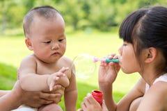 Bebé curioso tocar a las muchachas que soplan burbujas de jabón Fotografía de archivo