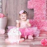 bebé de 1 año en vestido rosado con su primera torta de cumpleaños Imagen de archivo