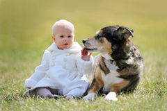 Bebé de 1 año precioso que se sienta afuera con el perro casero fotos de archivo