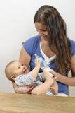 Bebé de alimentación de la madre con la botella de leche Foto de archivo