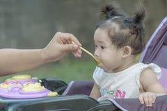 Bebé de alimentación de la madre con las gachas de avena Fotografía de archivo