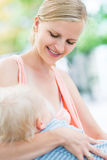 Bebé de amamantamiento de la madre al aire libre Fotografía de archivo