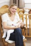 Bebé de amamantamiento de la madre en cuarto de niños Imagen de archivo libre de regalías