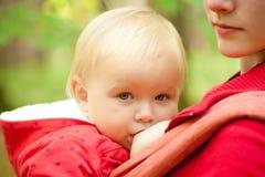 Bebé de amamantamiento de la madre en parque Imagen de archivo
