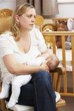 Bebé de amamantamiento de la madre preocupante en cuarto de niños Imagen de archivo