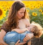 Bebé de amamantamiento de la mujer Fotografía de archivo