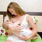 Bebé de amamantamiento en cama Fotos de archivo