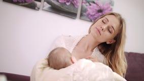 Bebé de amamantamiento de la mamá hermosa Hija de amamantamiento de la madre soñadora almacen de metraje de vídeo