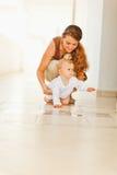 Bebé de ayuda de la madre feliz a arrastrarse Fotografía de archivo