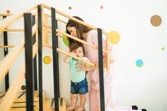 Bebé de ayuda del terapeuta subir las escaleras fotos de archivo libres de regalías