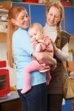 Bebé de caída de la madre en el cuarto de niños Imagenes de archivo