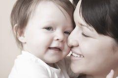 Bebé de caricia de la madre feliz foto de archivo
