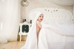 Bebé de cinco meses del bebé recién nacido en el dormitorio al lado de una cama blanca grande en el piso de madera envuelto en un Imagenes de archivo