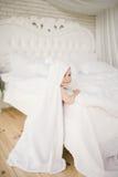 Bebé de cinco meses del bebé recién nacido en el dormitorio al lado de una cama blanca grande en el piso de madera envuelto en un Imagen de archivo libre de regalías