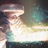 Bebé de Cristmas que sostiene el regalo con el polvo de hadas abstracto, la Navidad del stardust Foto de archivo