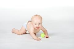 Bebé de de seis meses con el juguete en el fondo blanco Imagen de archivo libre de regalías
