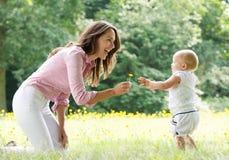 Bebé de enseñanza de la madre feliz a caminar en el parque Imagen de archivo