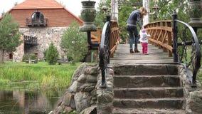 Bebé de enseñanza de la madre feliz a caminar en el puente de madera sobre el río en parque 4K