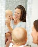 Bebé de enseñanza sonriente hermoso de la mujer cómo cepillar los dientes Imagen de archivo libre de regalías