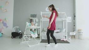 Bebé de entretenimiento de la mamá juguetona que se sienta en highchair almacen de metraje de vídeo