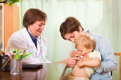 Bebé de examen del doctor Foto de archivo