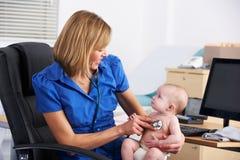 Bebé de examen del doctor BRITÁNICO Foto de archivo libre de regalías