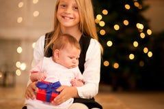 Bebé de la muchacha y de la hermana en la Navidad Fotografía de archivo