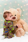 Bebé de la Navidad en los pijamas que sostienen el oso de peluche Fotos de archivo