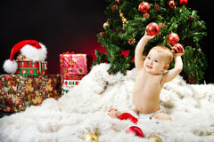 Bebé de la Navidad que se sienta en la piel con los regalos Fotos de archivo
