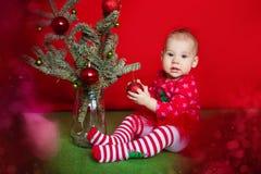 Bebé de la Navidad que sostiene la bola roja cerca de árbol de abeto del Año Nuevo Fotos de archivo