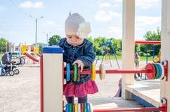 Bebé de la niña en el sombrero con una flor y una chaqueta azul del dril de algodón y un vestido rojo que juegan en el patio y la Imagen de archivo