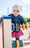 Bebé de la niña en el sombrero con una flor y una chaqueta azul del dril de algodón y un vestido rojo que juegan en el patio y la Imagenes de archivo