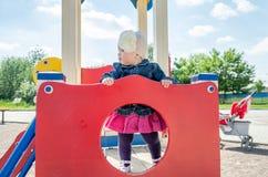 Bebé de la niña en el sombrero con una flor y una chaqueta azul del dril de algodón y un vestido rojo que juegan en el patio y la Fotografía de archivo libre de regalías