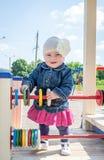 Bebé de la niña en el sombrero con una flor y una chaqueta azul del dril de algodón y un vestido rojo que juegan en el patio y la Fotos de archivo libres de regalías