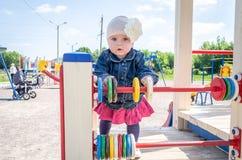 Bebé de la niña en el sombrero con una flor y una chaqueta azul del dril de algodón y un vestido rojo que juegan en el patio y la Fotos de archivo