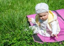 Bebé de la niña que juega en la hierba en un prado que se sienta en karemat Imagen de archivo libre de regalías