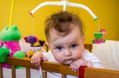 Bebé de la niña que se sienta en su cama Imágenes de archivo libres de regalías