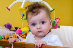 Bebé de la niña que se sienta en su cama Foto de archivo