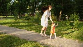 Bebé de los primeros pasos con la mamá Juegos de la mamá con su pequeña hija en parque del verano La mamá y el niño están en la t almacen de video