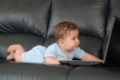 Bebé de mentira con la computadora portátil Fotos de archivo libres de regalías