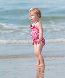 Bebé de mirada travieso en la playa Imagen de archivo