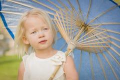 Bebé de ojos azules adorable que celebra el parasol afuera en el parque imagen de archivo
