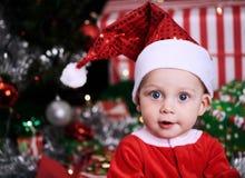Bebé de Papá Noel en el pensamiento que mira la cámara Foto de archivo libre de regalías