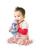 Bebé de risa asiático con la taza del canalón Foto de archivo libre de regalías