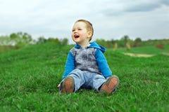 Bebé de riso feliz que senta-se no campo verde Fotografia de Stock Royalty Free