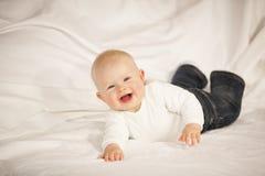 Bebé de riso que encontra-se em um sofá imagem de stock royalty free